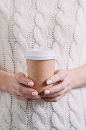 A woman in a white sweater holding a paper Cup of coffee. Template for text or design Standard-Bild - 121678508