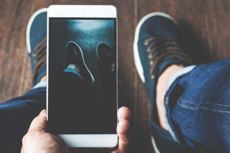 Young man taking pictures of sneakers on a mobile phone. Point of view