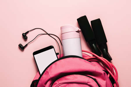 Sports bag and accessories on pink background