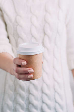 A woman in a white sweater holding a paper Cup of coffee. Template for text or design Standard-Bild - 121678605