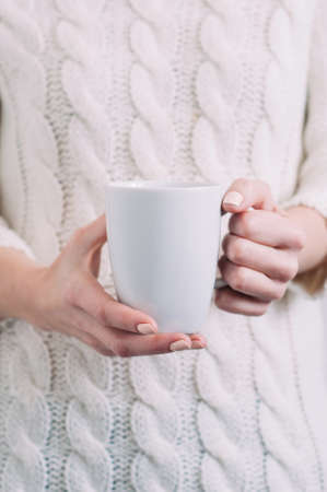 A woman in a white sweater holding a white mug in her hands. Template for text or design Standard-Bild - 121678607