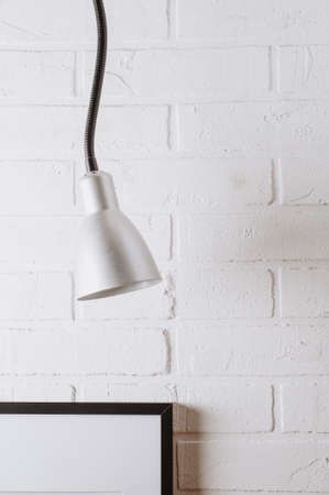 Old electric lamp on a background of white concrete wall. Workshop or studio concept