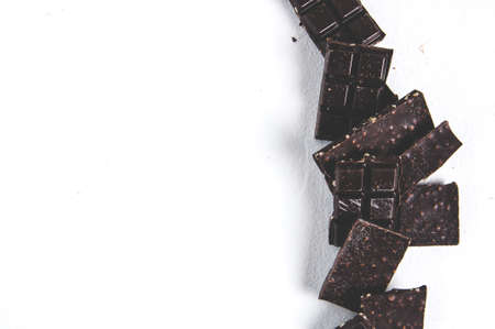 Pieces of dark chocolate on a light background