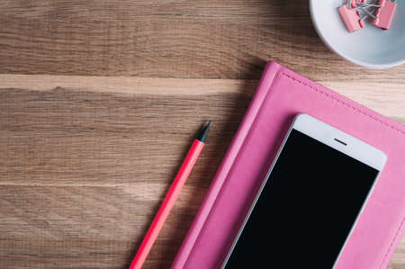 Pink notebooks and smartphone on the table