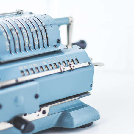 Old calculating machine on white background. Accounting or business concept Standard-Bild - 121679027