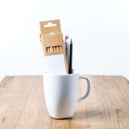 White mug on a wooden table. Template for text or design
