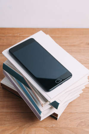 Black smartphone and a stack of books on a light background Standard-Bild - 121679153