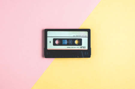 Old audio cassette tape on pink-yellow  background 스톡 콘텐츠