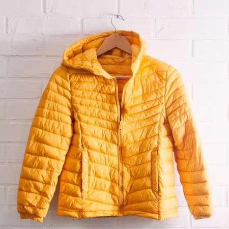 Yellow children's jacket on white brick wall
