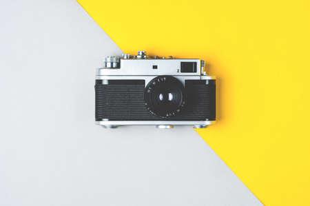 Old retro photo camera on grey-yellow background Imagens