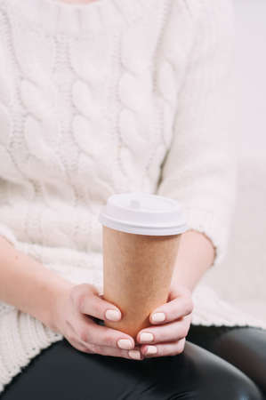 A woman in a white sweater holding a paper Cup of coffee. Template for text or design Standard-Bild - 121679218