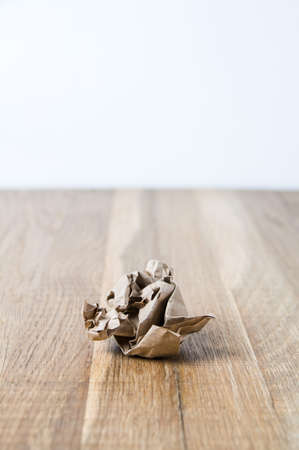 Crumpled paper on wooden table Stock Photo