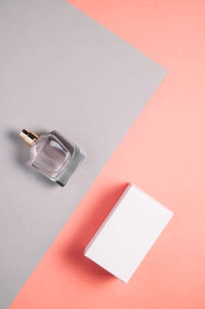 Perfume and box on a pale gray-pink background