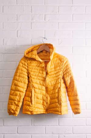 Yellow children's jacket on white brick wall Stock Photo - 121679454