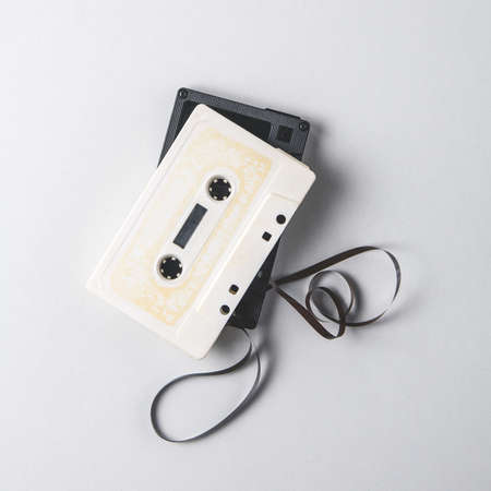 White and black audio cassettes on a light background. Place for text Archivio Fotografico