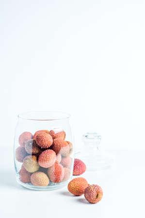 Fresh lychee in jar on white background