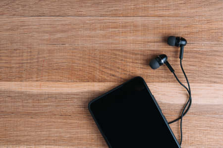 Black headphones and smartphone on wooden background
