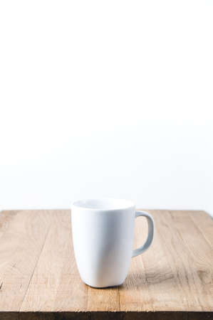 White mug on a wooden table. Template for text or design Standard-Bild - 121679836