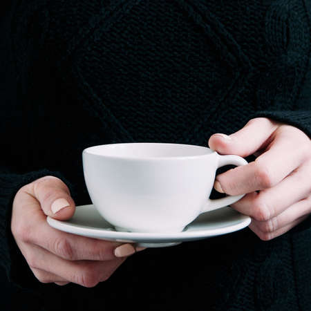 A woman in a black sweater holds a white mug in her hands. Template for text or design