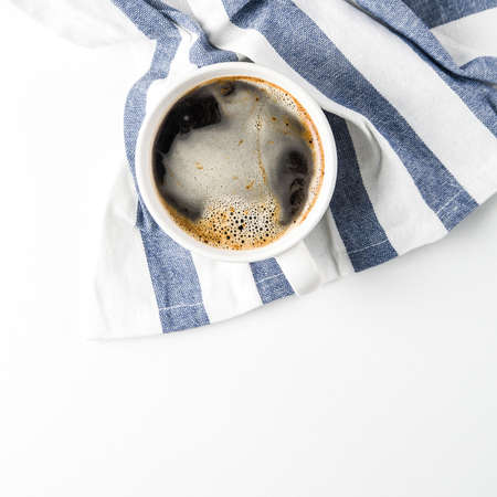 Cup of coffee on a towel with a blue stripe