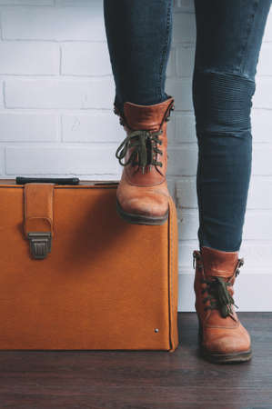Female legs shod in Hiking boots and an old suitcase. Travel concept Stok Fotoğraf