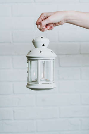 Woman holding a Christmas lantern on a white wall background