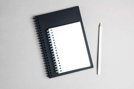 White Notepad and a white pencil on a light background. Place for text