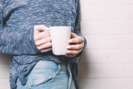 A woman holding a white mug in her hands. Template for design or text Stockfoto