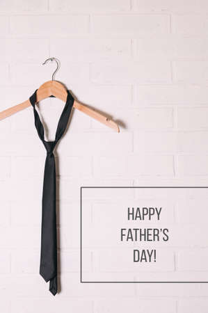 Tie on a hanger in front of a white wall