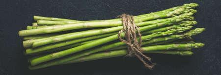 Fresh green asparagus on dark concrete background