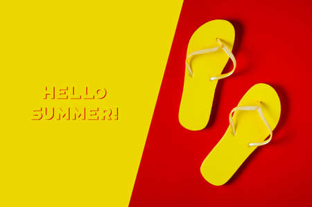 Yellow flip-flops on red-yellow background. Space for text or design 版權商用圖片