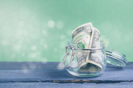 Two dollars in the jar on a green background. Savings money concept
