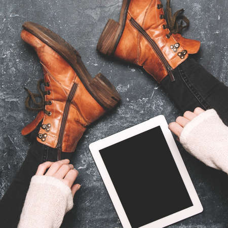 Female legs shod in Hiking boots and tablet pc. Mockup for text or apps