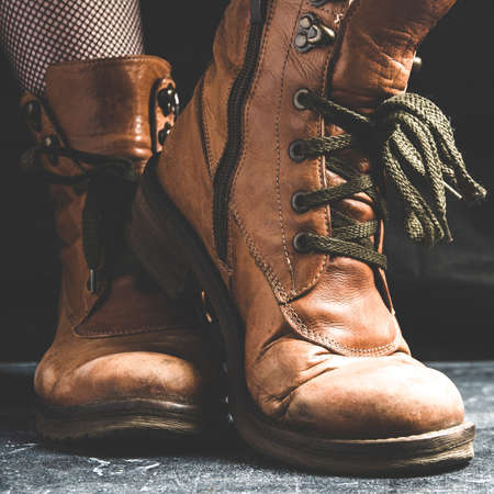 Female legs shod in old Hiking boots