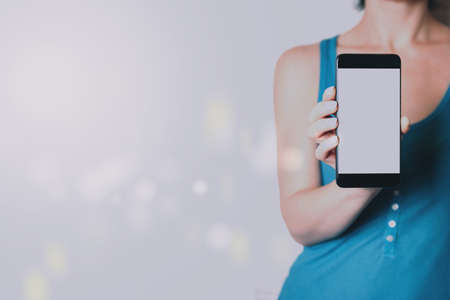 A woman holding a smartphone in her hands. Template for design or app