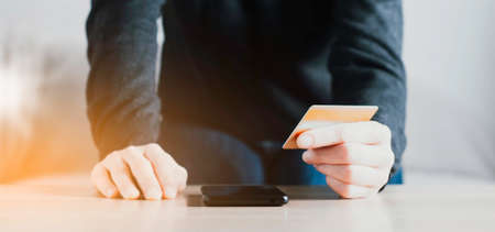 A woman holding a smartphone and credit card in her hands. The concept of online shopping or money transfer Stock Photo