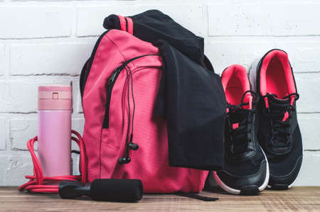 Pink backpack with sportswear, sneakers and a jump rope. The concept of fitness or running