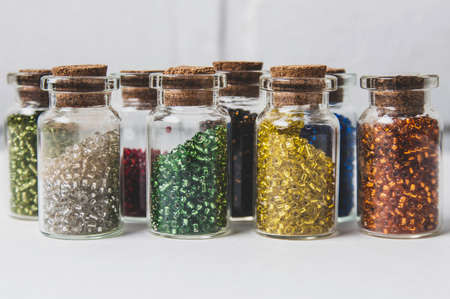 Jars with colored beads on a pale background