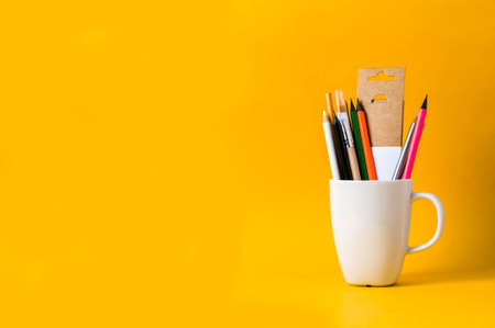 Colored pencils in white Cup on yellow background