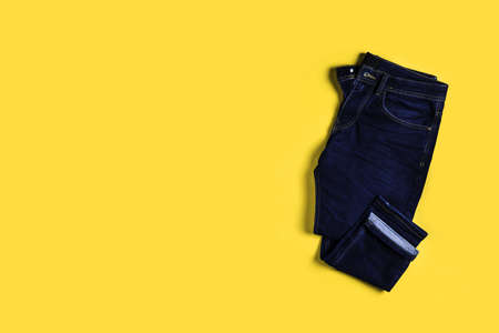 Skinny jeans on yellow background 스톡 콘텐츠 - 129147733