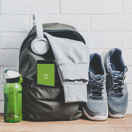 Green backpack with sportswear and sneakers. The concept of fitness or running Stock Photo
