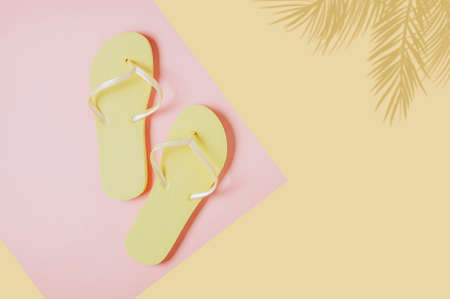 Yellow flip-flops on pink-yellow background. Space for text or design Standard-Bild - 129148802