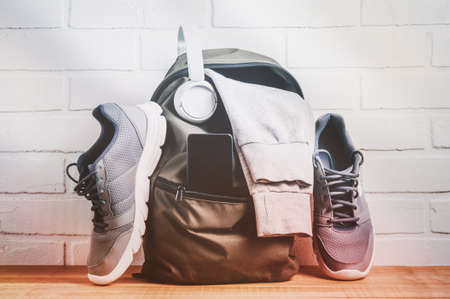 Green backpack with sportswear and sneakers. The concept of fitness or running 免版税图像