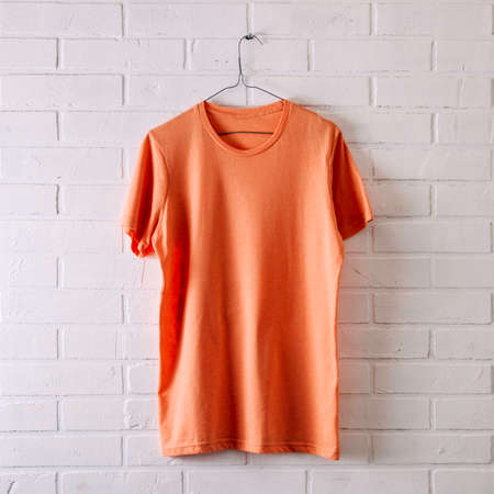 Orange t-shirt on a pale background. Template for text or design