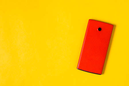 Red smartphone on yellow  background