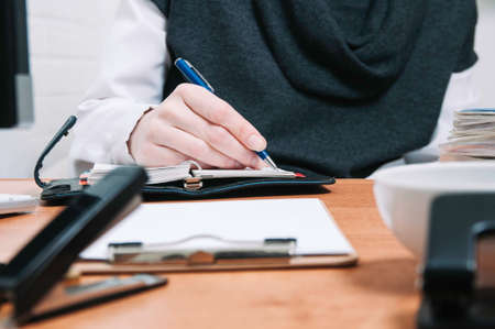 Business woman writes in a notebook. The concept of office work