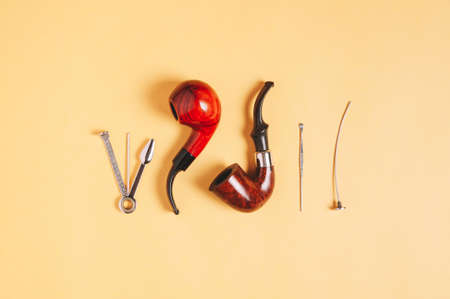 Smoking pipe and accessories on yellow background Фото со стока
