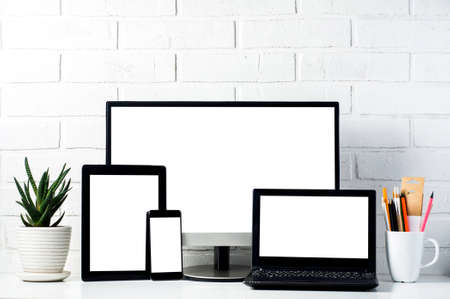 Monitors and tablets on a light background. Template for text or design of the website Фото со стока