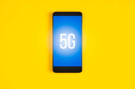 Black smartphone on yellow background. Template for text or design