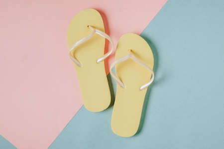 Yellow flip-flops on pink-green background. Space for text or design